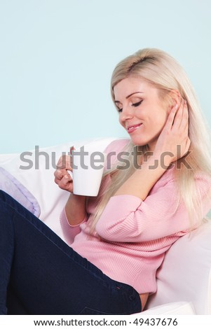 Blond woman sat in an armchair with a mug of tea.