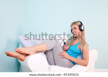 Blond woman sat in an armchair with headphones on listening to music.