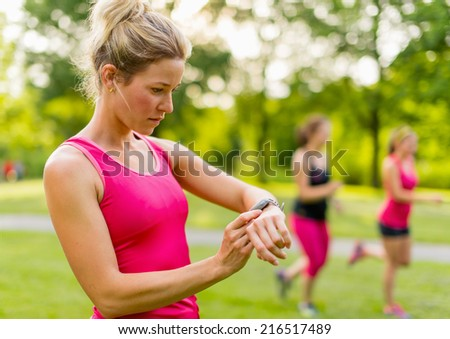 blond woman setting her timer before jogging - stock photo