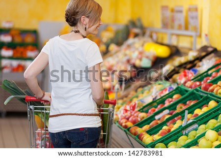 Blond woman shopping for groceries in a supermarket standing with her back to the camera pushing her trolley past the fresh produce - stock photo