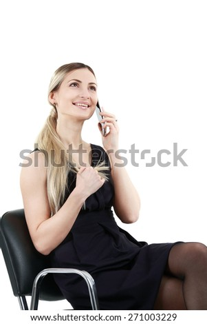 Blond woman sitting on the chair and talking on phone - stock photo