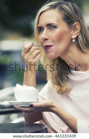 blond woman sitting outside at cafe and drinking hot chocolate with whipped cream