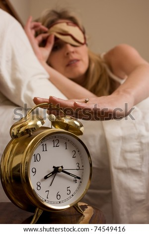 Blond woman sleeping in bed peeking out from cover over eyes looking at the clock and reaching to turn off a round gold alarm clock time is after eight o'clock