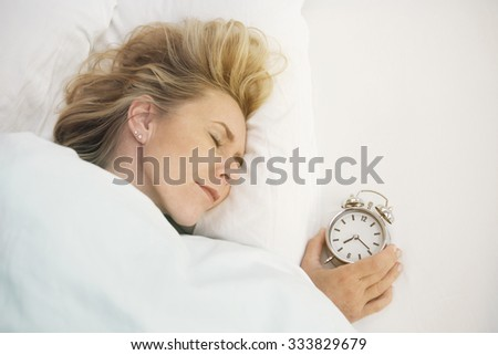 blond woman sleeping in bed with alarm clock next to her