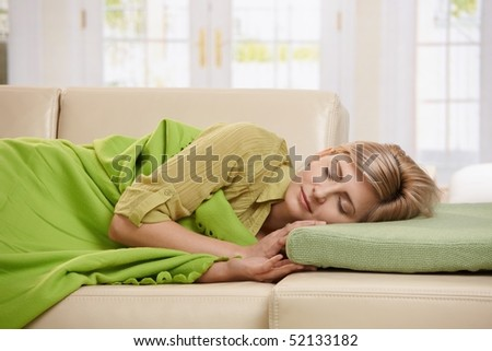 Blond woman sleeping with blanket on couch in sunlit living room at home. - stock photo