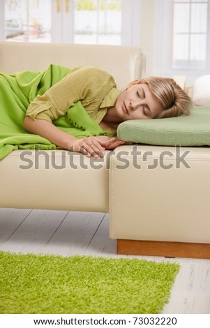 Blond woman sleeping with blanket on couch in sunlit living room at home.? - stock photo