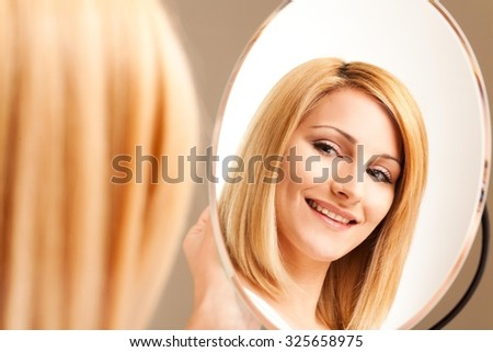 Blond woman smiling in the mirror. - stock photo