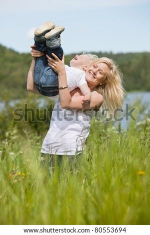 Blond woman standing in meadow playing with toddler son - stock photo
