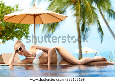 Blond woman sunbathing on an infinity pool under a beach umbrella at a tropical resort lying on the pool edge in her bikini smiling at the camera with palm trees behind - stock photo