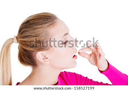 Blond woman taking pill, isolated on white. - stock photo