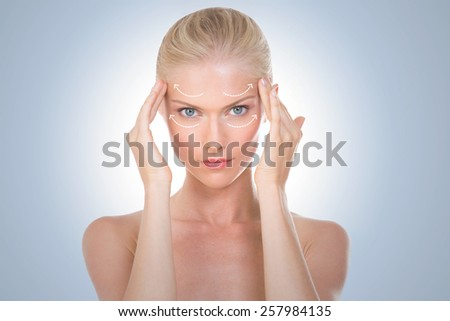 blond woman touching her head - stock photo