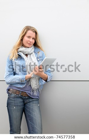 Blond woman using electronic tablet - stock photo