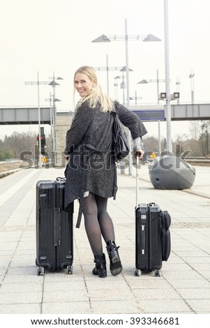 blond woman walking at train station with her suitcases and smiles at camera - stock photo