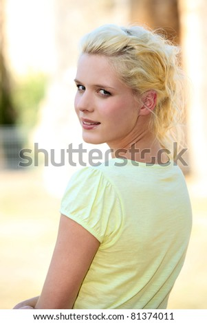Blond woman walking down sunny street - stock photo