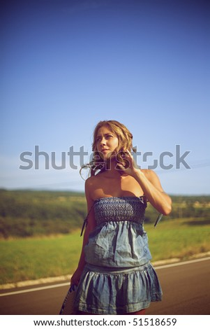 Blond woman walking on the road - stock photo