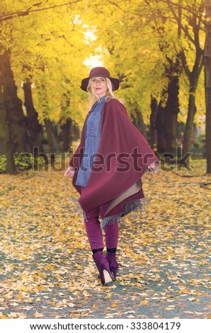 blond woman walking underneath colorful trees in autumn - stock photo