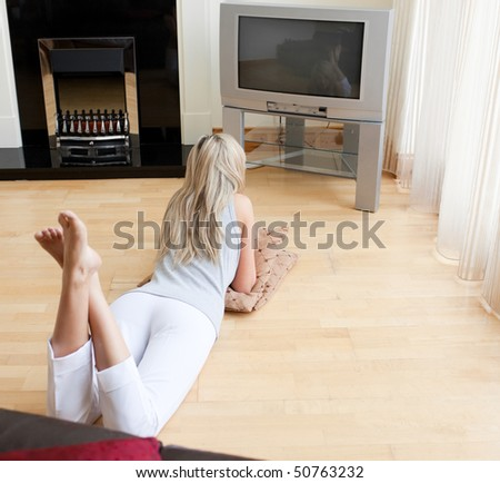 Blond woman watching TV lying on the floor in a living-room - stock photo