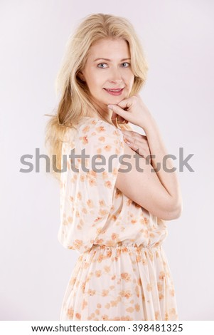 blond woman wearing beige dress on white background