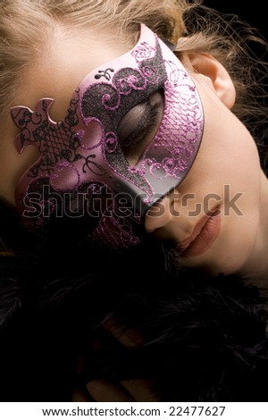 blond woman wearing purple Venetian mask and black feathers - stock photo