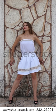 Blond woman wearing white dress leaning on textured wall - stock photo