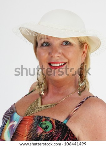 Blond woman wearing white hat with brightly colored dress - stock photo