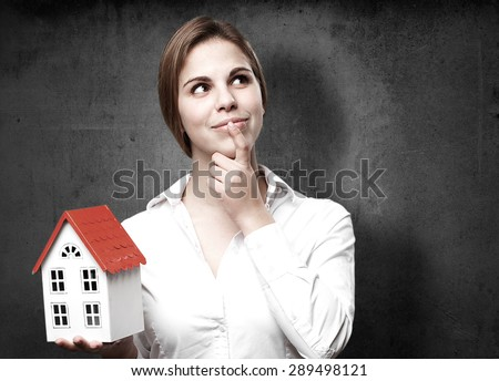 blond woman with a small house thinking - stock photo