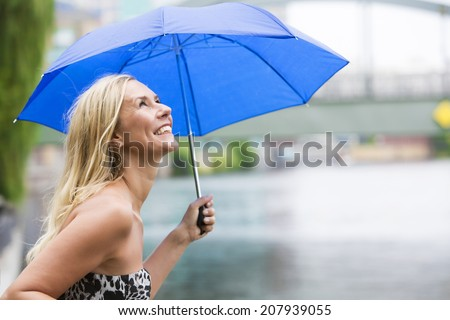 blond woman with an umbrella standing by a river and enjoying the rainy weather - stock photo