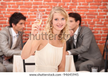 Blond woman with champagne in restaurant - stock photo