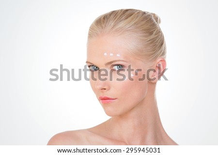 blond woman with cream on her front and her cheekbone