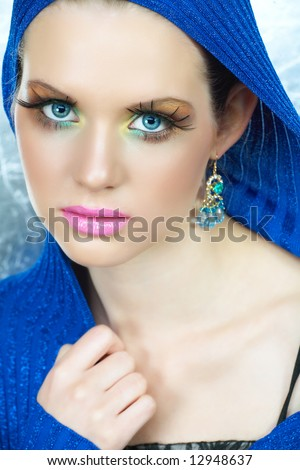 Blond woman with high-fashion make-up in blue metallic top with a cape and blue eyes - stock photo