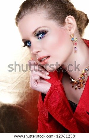 Blond woman with high-fashion make-up in red jacket holding her collar and smiling - stock photo
