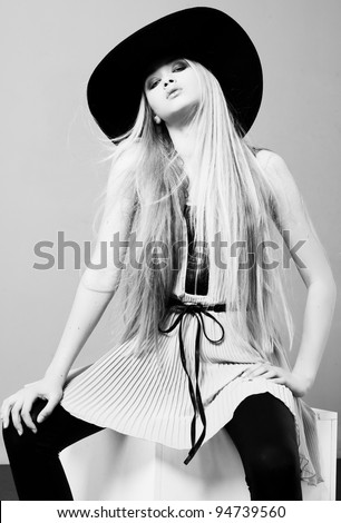 Blond woman  with long beautiful hair and smoky eyes in a hat. Studio - stock photo