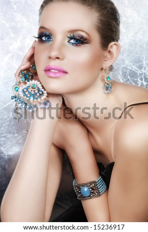 Blond woman with long false lashes holding pearl and blue stones golden jewelry with dreaming expression - stock photo