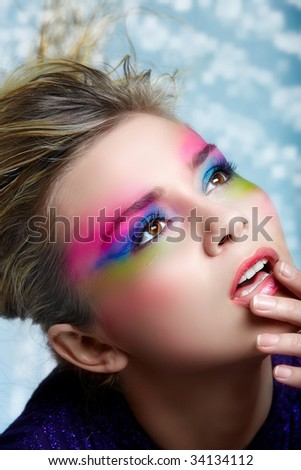 Blond woman with pink, purple and green eye make-up - stock photo