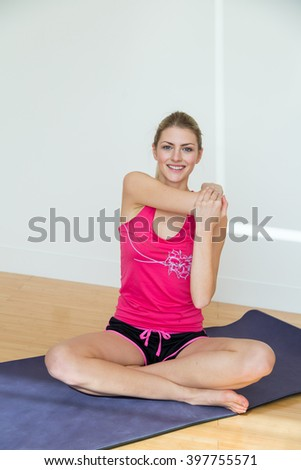 Blond woman with ponytail wearing pink top and black shorts stretches one arm overhead while seated on a yoga mat - stock photo