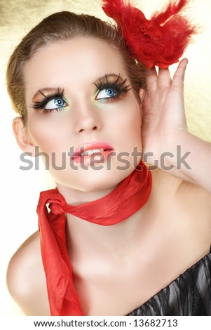 Blond woman with red rose in her hair and scarf listening with a hand next to her face, long feather false lashes - stock photo