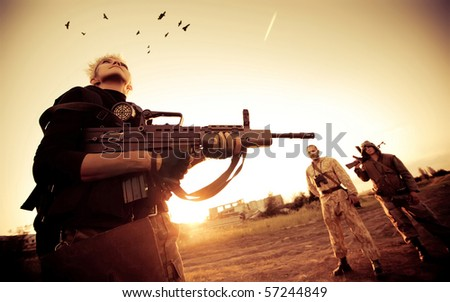 Blond woman with rifle is looking at ravens. Two rebels with Kalashnikov machine gun on the background. - stock photo