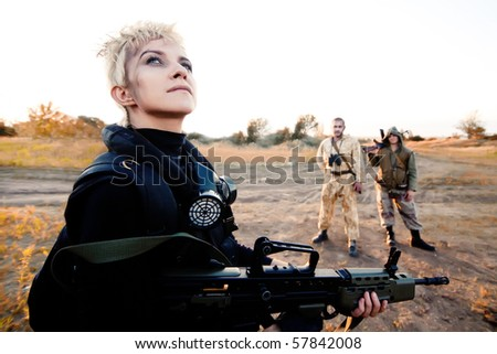 Blond woman with rifle. Two rebels with Kalashnikov machine gun on the background. - stock photo