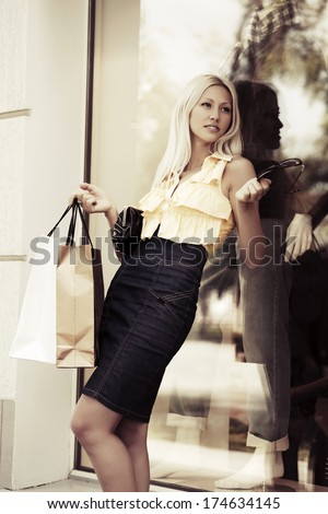 Blond woman with shopping at the mall window - stock photo