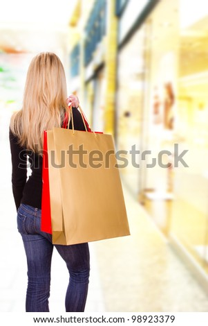 Blond woman with shopping bags in shopping center, back view - stock photo