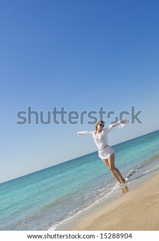 blond woman with white scarf dancing on the shore of a a Mediterranean beach - stock photo