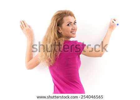 Blond woman writing on copyspace virtual screen. back view of girl drawing on screen with blue marker on white background  - stock photo