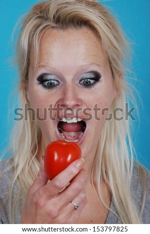 Blond womanl eating a tomato