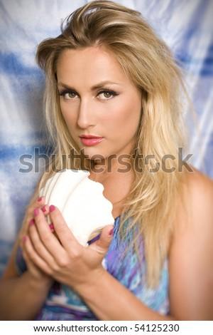 blond women hold white shell - stock photo