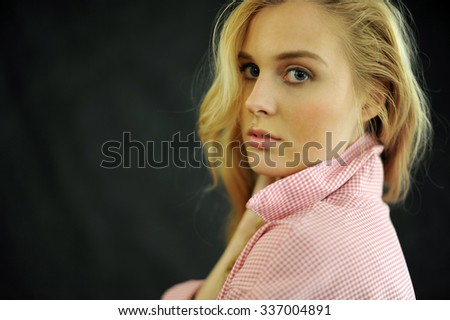 Blond women wear red shirt on dark background