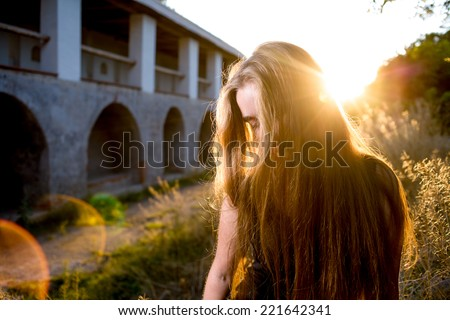 Blond women with long hair posing backlit at sunset with her pretty face hide by her hair, lens flares - stock photo