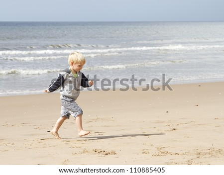 Blond young boy running on the beach - stock photo