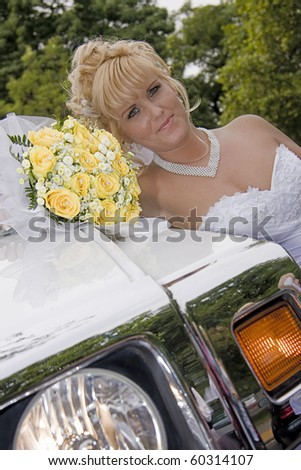 blond young bride beside a car - stock photo