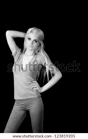 blond young fashion model posing at black background - stock photo