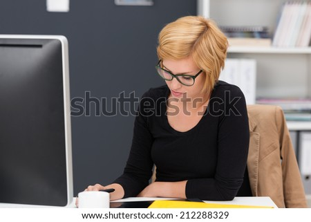 Blond young female dedicated employee focused on the draft of a document, while working behind the monitor, at her desk, in the office - stock photo